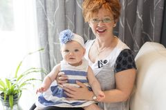 Grandmother hold little baby girl cute smiling close-up in sofa. A Grandmother hold little baby girl cute smiling close-up Royalty Free Stock Photo