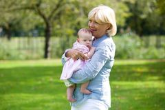 Grandmother holding baby granddaughter royalty free stock photography