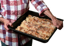 Grandmother holding a baking tray with apple strud Royalty Free Stock Photography
