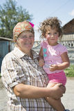 Grandmother holding a curly little granddaughter in her arms. Royalty Free Stock Photos