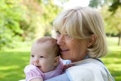 Grandmother holding granddaughter outdoors Stock Photo