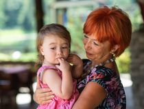 Grandmother holding her granddaughter, family idyll. 2 royalty free stock image