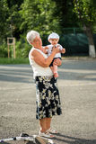 Grandmother holding her nephew in her arms, outdoors Royalty Free Stock Photo