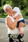 Grandmother holding her nephew in her arms, outdoors Stock Photo