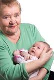 Grandmother holding newborn baby. Great grandmother sitting and tenderly holding newborn grandson isolated on white background Stock Photo