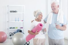 Grandmother holding pink fitness mat. And smiling to grandfather before yoga classes in fitness studio Royalty Free Stock Images