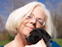 Grandmother Holding A Puppy. A close-up of a grandmother smiling and holding a German Shorthair puppy outside Stock Photography