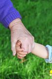 Grandmother holds child hand Stock Photography