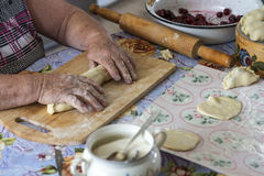 Grandmother home cooks the dumplings Royalty Free Stock Photography