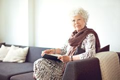 Grandmother at Home Sitting on the Couch. Relaxed grandmother sitting on the couch at home Royalty Free Stock Photos