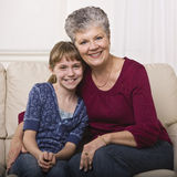 Grandmother Hugging Granddaughter. A grandmother is sitting on a couch and hugging her granddaughter.  They are smiling at the camera.  Square framed shot Royalty Free Stock Photography