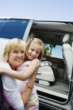 Grandmother Hugging Granddaughter By Minivan Stock Image