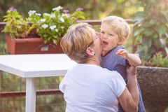 Grandmother and grandchild kisses. Grandmother hugs and gently kisses her grandchild in garden, natural light royalty free stock photography