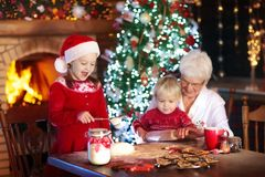 Grandmother and kids bake Christmas cookies. Royalty Free Stock Images