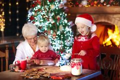 Grandmother and kids bake Christmas cookies. Grandmother and children baking Christmas cookies at fire place and Xmas tree. Kids and grandma bake sweets. Family Royalty Free Stock Photo