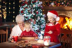 Grandmother and kids bake Christmas cookies. Grandmother and children baking Christmas cookies at fire place and Xmas tree. Kids and grandma bake sweets. Family Stock Photo