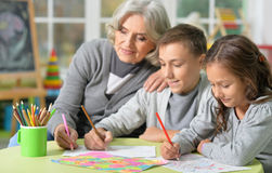 Grandmother with kids drawing Stock Photos
