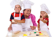 Grandmother with kids making cookies. Grandmother with kids in chef hats making cookies, playing with the dough - isolated Royalty Free Stock Photography