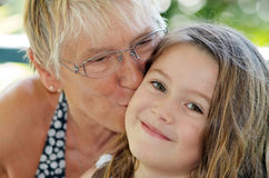 Grandmother kiss. Headshot portrait of grandmother tenderly kissing her smiling granddaughter Stock Photo