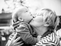 Grandmother kiss her grandson, love moment. Grandmother with baby boy, happy love moment together, monochrome Royalty Free Stock Photo