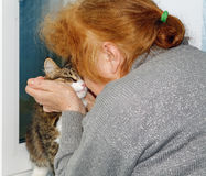 Grandmother kisses the cat Royalty Free Stock Images