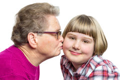 Grandmother kisses grandchild on cheek Stock Images