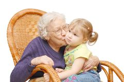 Grandmother kisses the granddaughter. In an armchair Stock Photos
