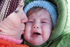 Grandmother kissing crying baby. Royalty Free Stock Photo