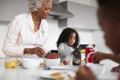 Grandmother In Kitchen With Grandchildren Making Pancakes Together royalty free stock photography