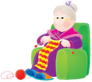 Grandmother knits a scarf. Granny sits in a armchair and knits a striped scarf Stock Images