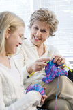 Grandmother knitting with granddaughter. Focus on senior woman Royalty Free Stock Image