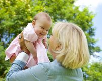 Grandmother lifting grandchild up and playing Stock Image