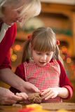 Grandmother and little girl baking Christmas cookies Royalty Free Stock Images