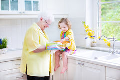 Grandmother and little girl baking pie in white kitchen. Happy beautiful great grandmother and her adorable granddaughter, curly toddler girl in colorful dress Royalty Free Stock Photos