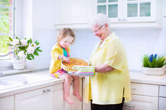 Grandmother and little girl baking pie in white kitchen. Happy beautiful great grandmother and her adorable granddaughter, curly toddler girl in colorful dress Royalty Free Stock Photography