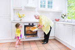 Grandmother and little girl baking pie in white kitchen. Happy beautiful great grandmother and her adorable granddaughter, curly toddler girl in colorful dress Stock Images