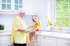 Grandmother and little girl baking pie in white kitchen. Happy beautiful great grandmother and her adorable granddaughter, curly toddler girl in colorful dress Royalty Free Stock Photo