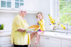 Grandmother and little girl baking pie in white kitchen Royalty Free Stock Photography