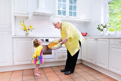 Grandmother and little girl baking pie in white kitchen. Happy beautiful great grandmother and her adorable granddaughter, cute curly toddler girl in a colorful Stock Images