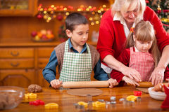 Grandmother and little girl and boy baking Christmas cakes in th royalty free stock images