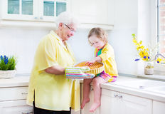 Grandmother and little girl cooking pie in white kitchen. Happy beautiful great grandmother and her adorable granddaughter, curly toddler girl in colorful dress Royalty Free Stock Photo