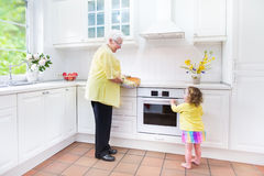Grandmother and little girl cookinga pie in white kitchen. Happy beautiful great grandmother and her adorable granddaughter, curly toddler girl in colorful dress Royalty Free Stock Photo