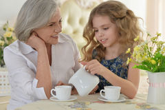 Grandmother with little girl drinking tea Stock Photography