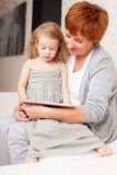 Grandmother and little girl at home on sofa. Family wiht tablet computer at sofa. Grandmother and little girl at home on sofa. Generation Stock Images