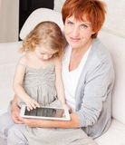 Grandmother and little girl at home on sofa Royalty Free Stock Image