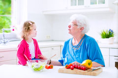 Grandmother and little girl making salad Royalty Free Stock Photography