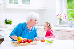 Grandmother and little girl making salad Stock Photography
