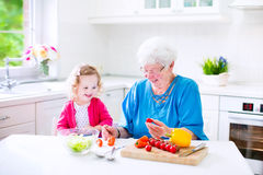 Grandmother and little girl making salad Stock Images