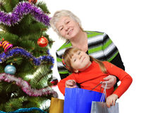 Grandmother and little near Christmas tree. Royalty Free Stock Photos