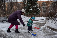 Grandmother and little two-year-old grandson have fun playing hockey in the park in winter royalty free stock image